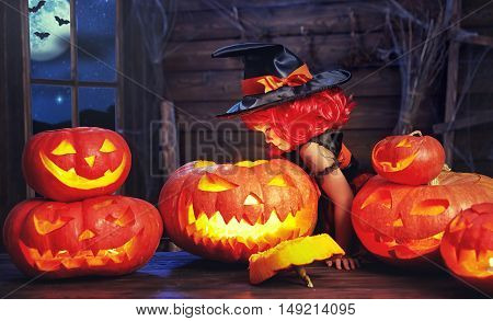 Halloween. child little witch with lantern pumpkin Jack in the old hut
