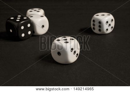White and black gambling dices on dark background