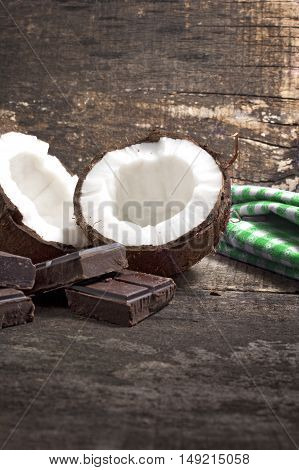 Coconut with chocolate on old wooden background