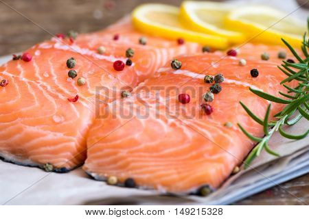 Detail of Raw Salmon Fish Fillet with Lemon Spices and Fresh Herbs Ready for Cooking