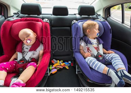 Little boy and girl twins are sleeping in the car on child safety seats