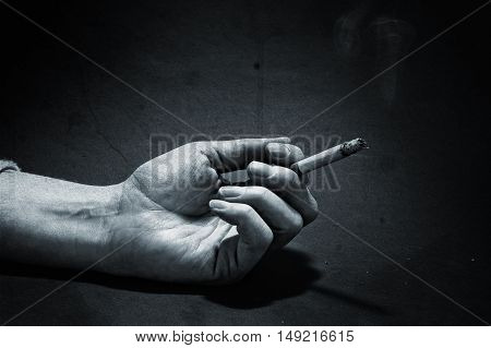 Hand with burning cigarette over a grunge background