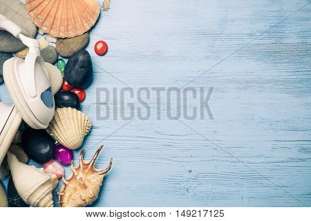 White headphones among sea shells and stones on wooden surface