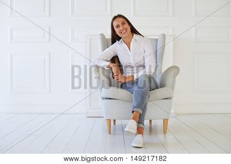 Young smiling woman, crossed her legs and sitting in a modern armchair relaxing in her room