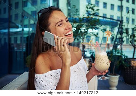 Young dark-haired female with cocktail in her hand is cheerfully speaking on the phone on open terrace near building with mirror windows