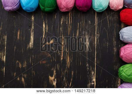Top view of partially seen multicolor skeins lying on dark wooden background