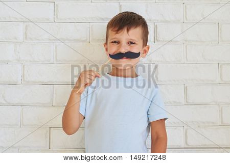 Young gentleman holding paper moustache with rather mischievous facial expression standing against white wall