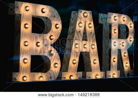 Vintage bar sign illuminated against a dark background