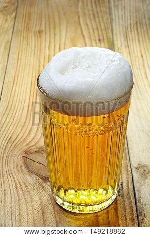 Faceted glass of beer on wooden table
