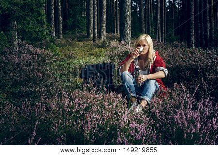 Young active woman tourist drinking tea from a thermos and sitting in the forest. Tourism. Healthy active lifestyle concept