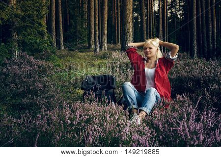 Young active woman tourist resting on the lawn in the forest. Healthy active lifestyle concept. Tourism.