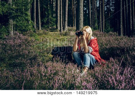Young active woman tourist sits in a clearing in the woods and looking through binoculars. Healthy active lifestyle concept. Tourism.