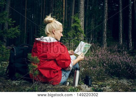 Young active woman sitting in a clearing in the forest holding and watching map. Healthy active lifestyle concept. Tourism.