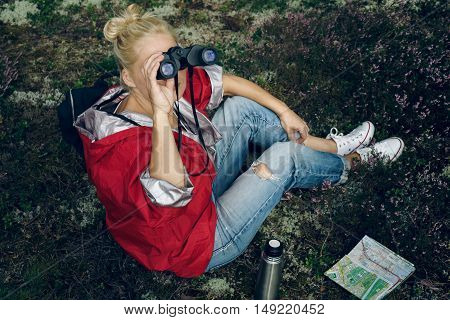 Young active woman tourist sit in a clearing in the woods with a backpack, holding binoculars and a map and looking at the forest. Healthy active lifestyle concept. Tourism.