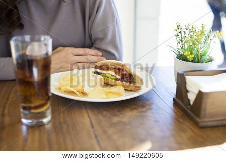 hands of brunette woman mauve color sweater on light brown wooden table with bacon cheese lettuce panini sandwich chips white dish cola glass flower pot and napkin holder
