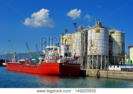 Red General Cargo ship on terminal in sea port