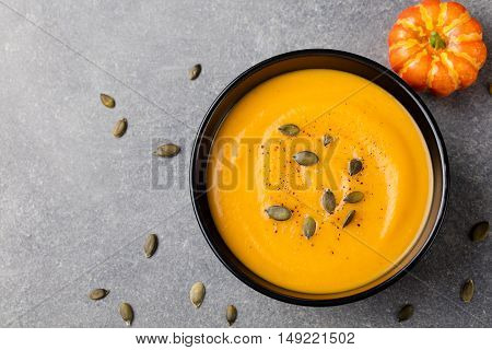 Pumpkin cream soup with pumpkin seeds in a black bowl. Grey stone background Top view Copy space