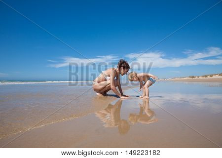 Baby And Mother Looking At Seaside