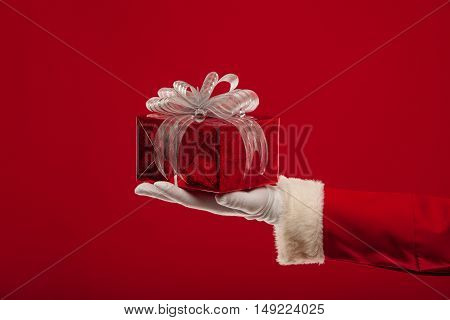 christmas Photo of Santa Claus gloved hand with red giftbox, on a red background