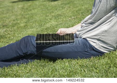 Tablet In Legs Sitting On Grass