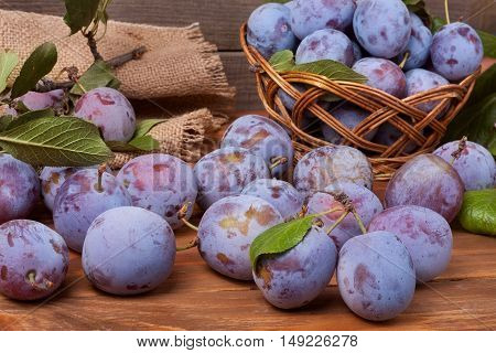 plum in a wicker basket on the wooden background with sackcloth.