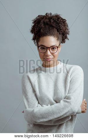 Portrait of young woman wearing glasses against gray background