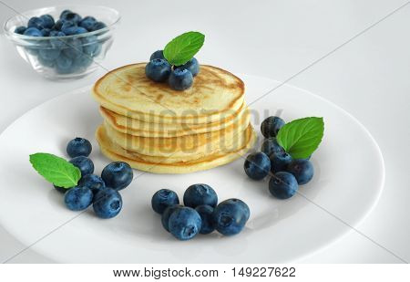 Blueberry pancakes gourmet breakfast background with mint leaves and maple syrup.