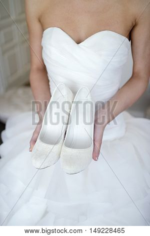 Beautiful bride in white wedding dress is holding shoes in her hands. Beauty model girl in bridal gown for marriage. Female portrait with boots. Close-up woman's arms. Cute lady indoors
