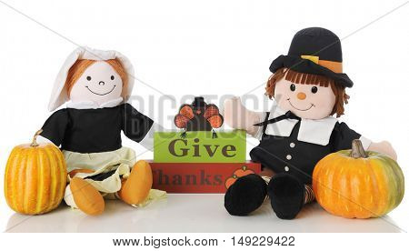 Two happy pilgrim dolls sitting by a