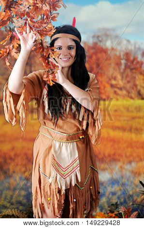 A beautiful Indian maiden looking at the viewer from behind colorful, low-hanging leaves.  Shes in a autumn wetland setting.