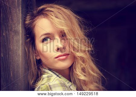 Portrait of a Dreamy Hipster Girl on Wooden Background. Romantic Woman. Toned Photo with Copy Space.