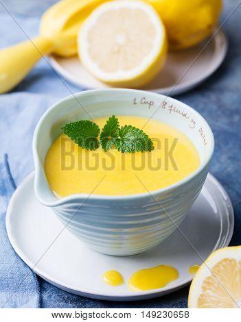 Lemon curd in ceramic bowl with fresh lemons on a blue napkin background Selective focus