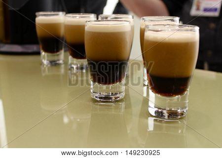 Two little shots of black beer, degustation, tasting by temptation