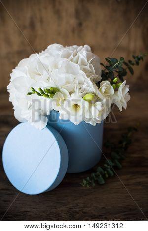 Bouquet of white hydrangeas in round  blue box, vintage postcard style