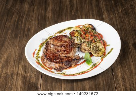 Grilled meat steak served on a white plate with grilled vegetables and sauce. On old wooden table
