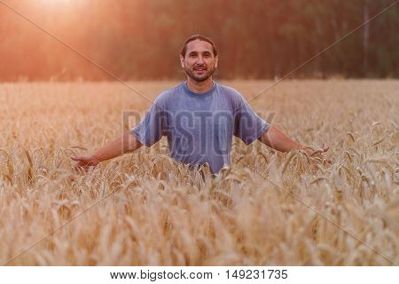 Happy people in a field of wheat touched by the hands and ears of wheat in sunset light.