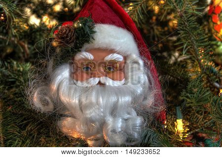 Close up of decoration of Santa Claus face with glasses in a Christmas tree.