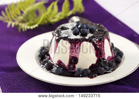 Sweet pudding with blueberry confiture on a plate