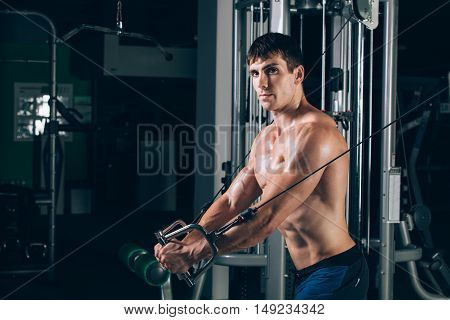 handsome bodybuilder works out pushing up excercise in gym.