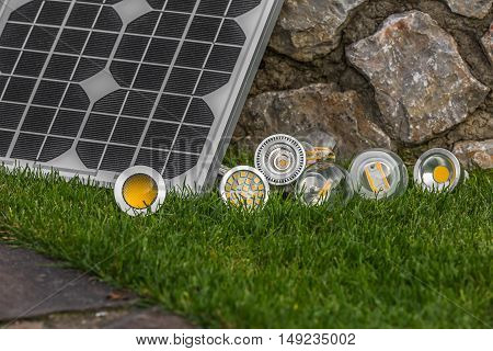 solar panel and various E27 bulbs LED halogen and tungsten bulbs some on the grass ( selective focus )