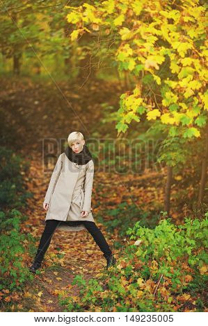 Portrait of young attractive blonde posing on the background of autumn forest in full growth.