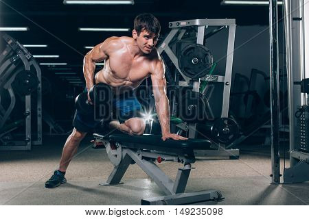 sport, fitness, lifestyle and people concept - flexing muscles with dumbbells in gym.