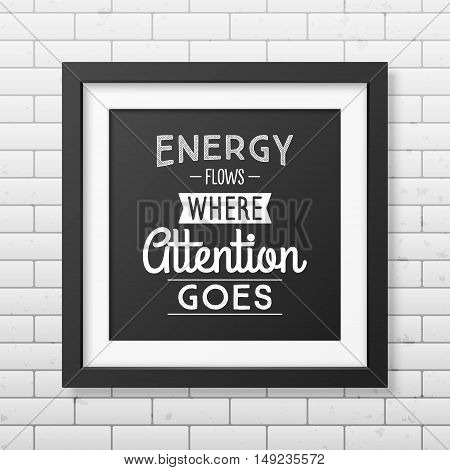 Energy flows where attention goes - Typographical Poster in the realistic square black frame on the brick wall background. Vector EPS10 illustration.