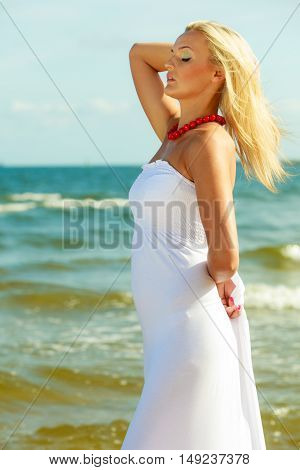 Girl posing in front of sea. Woman taking walk on sunny beach. Leisure relax outdoor concept.