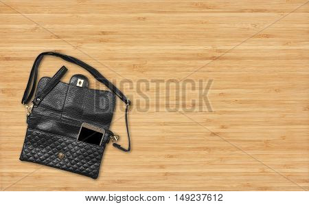 luxury leather black bag or wallet with smart phone on top view wood table business and fashion trend