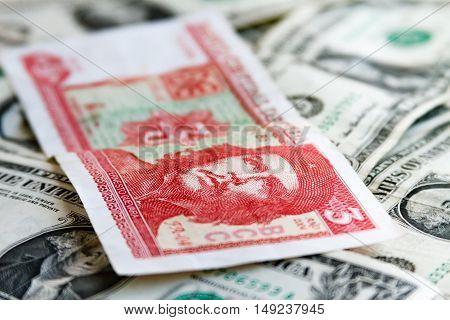 Three Cuban Pesos Bill Over Several Dollar Bills