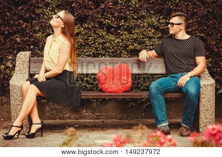 Love romance valentines dating concept. Upset girl on bench with boy. Angry young woman turns her back on boyfriend.