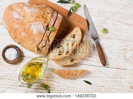 Top view of traditional white bread with olives and salt olive oil on a rustic wooden background with copy space.