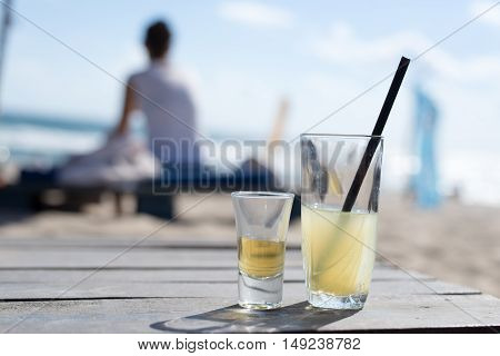 Homemade lemonade and brandy on the background of the beach on Durban pallet