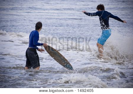 Skim Boarders In The Waves